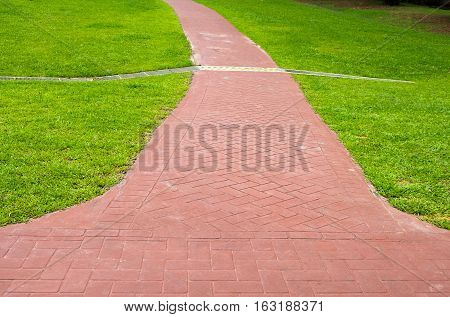Green park path way in vanishing perspective Walkway through green grass fieldRed stone walking path in a grass field