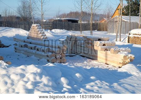 Lumber construction for house. Many smooth logs prepared for construction lying in rows on snow in clear sunny day. Horizontal photo
