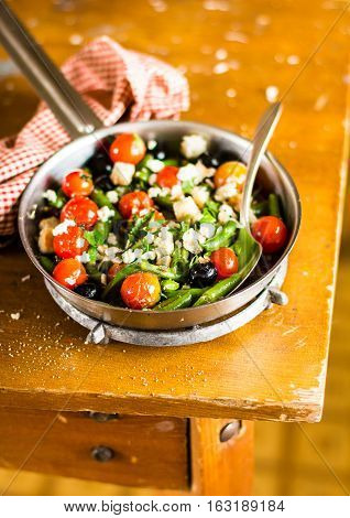 Warm salad with french beans, cherry tomatoes, black olives, feta cheese and wheat croutons in a pan, selective focus