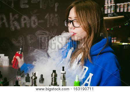 Young Cute Woman, The Seller In Vape Shop Shop, Smoking Electronic Cigarette,  Vaping And Releases A