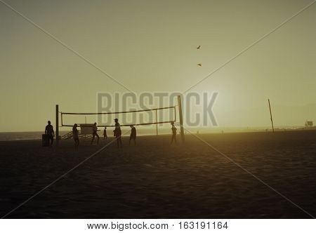 Young people playing volleyball in the sunset