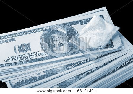 Cocaine In Plastic Packet On Stack Of Dollar Banknotes Over Black Background