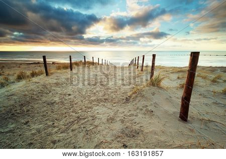 sand path to North sea beach at sunset Holland