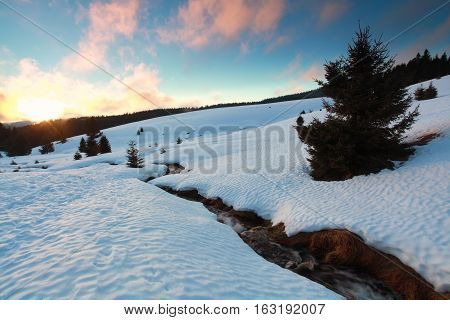evening sunlight over mountain sriver in winter