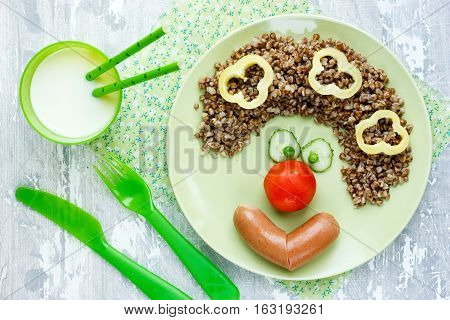 Healthy buckwheat - funny clown face from boiled buckwheat with sausage and vegetables creative idea for kids dinner or breakfast