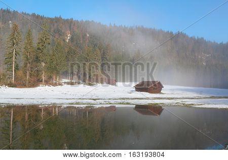 wooden trekker's hut reflected in water in winter foreest