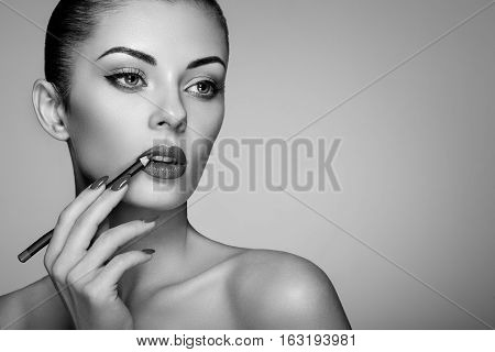 Beautiful woman paints lips with lipstick. Beautiful woman face. Makeup detail. Beauty girl with perfect skin. Red lips and nails manicure. Black and White