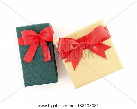 two gift boxes (green and golden) with red ribbon bow isolated on white background, top view