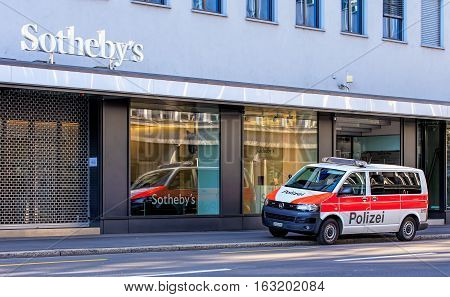 Zurich, Switzerland - 27 December, 2016: a Zurich Municipal Police van parked with flashing lights on Tahlstrasse street, windows of the Sotheby's office. Zurich Municipal Police is the third largest police corps in Switzerland.