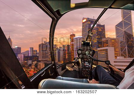Helicopter cockpit flying aerial view of cityscape of landmark buildings along the Lung Wo Road, a road between Central and Wan Chai district in Hong Kong island at sunset.