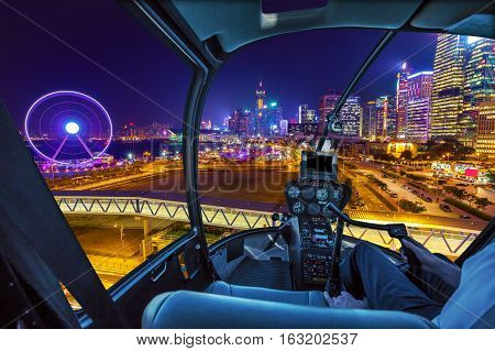 Helicopter cockpit aerial view of cityscape in Hong Kong, Central District, with Observation Ferris Wheel at Victoria Harbour illuminated at night.