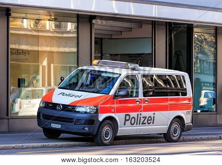 Zurich, Switzerland - 27 December, 2016: a Zurich Municipal Police van parked with flashing lights on Tahlstrasse street, a window of the Sotheby's office in the background. Zurich Municipal Police is the third largest police corps in Switzerland.