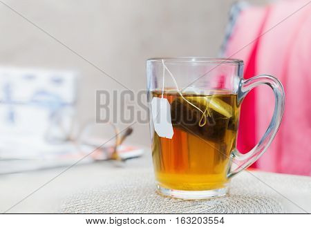 Close view of a glass of tea with a teabag on a table