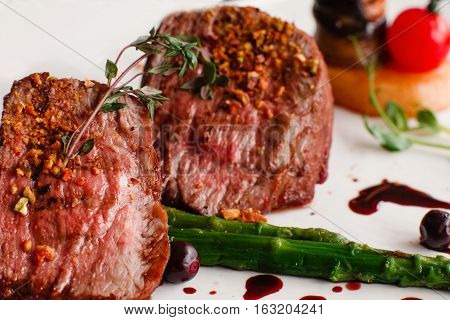 Medallions of grilled veal with asparagus close-up. Two pieces of roasted tenderloin with vegetables. Restaurant menu, healthy food, gourmet meal concept
