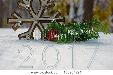 Fresh outdoor snow Happy New Year 2017 greeting message with evergreen branches in forest for nature theme, room for copy or logo for resort,healthy outdoor lifestyle New Years wishes for social network community image