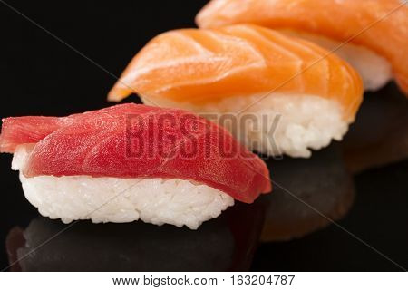 Close-up of Maguro and Salmon sushi on black background with reflection. Selective focus.