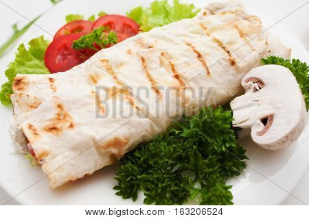 Burrito with fresh mushroom and parsley close up. Grilled shawarma served with vegetables. Turkish sandwich, mediterranean cuisine, junk food concept
