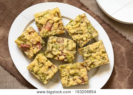 Freshly baked rhubarb crumble cake pieces on plate photographed overhead with natural light (Selective Focus Focus on the top of the cake pieces)