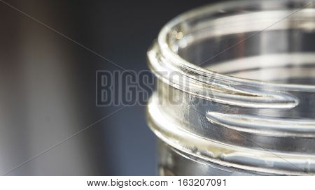Rim of a glass canning jar showing threads.