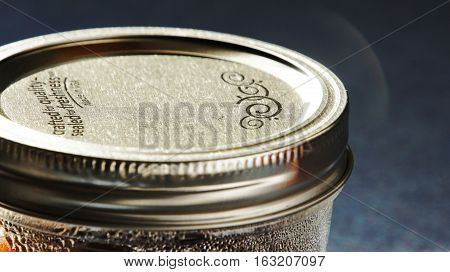 A shiny silver canning jar lid with black detailing.