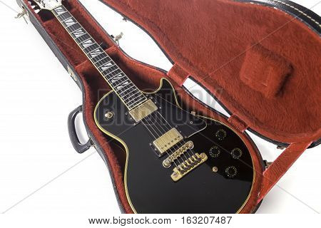 Classic black and gold electric rock guitar in red fur-lined case