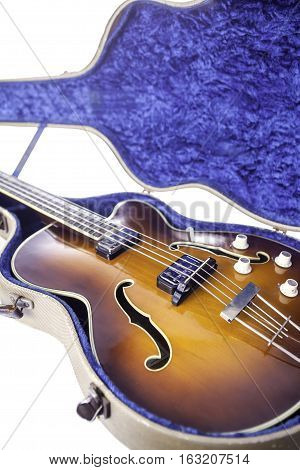 A vintage semi-acoustic archtop bass guitar with sunburst finish in original tweed case.