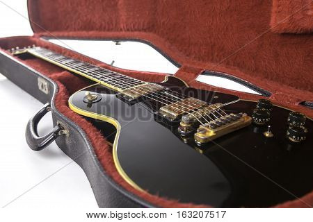 Classic black and gold eletric guitar in red fur-lined guitar. Sexy status symbol and ultimate rock guitar.