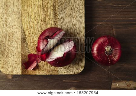 Red bisect onion on wooden table. Close-up from above.