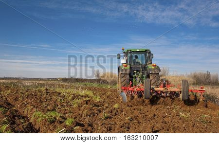 Farm tractor preparing the soil and ranking the field before planting Montijo Badajoz Extremadura Spain