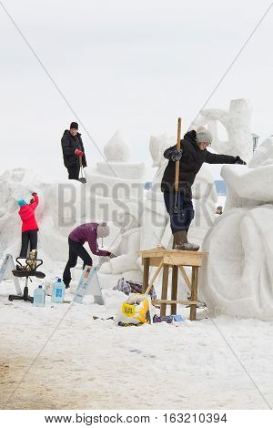 PETROZAVODSK, RUSSIA - FEBRUARY 20TH, 2016: craftsmen sculpt a snow sculpture on the International Winter Festival