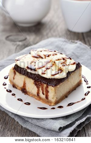 Cheese cake with chocolate syrup and piece of banana