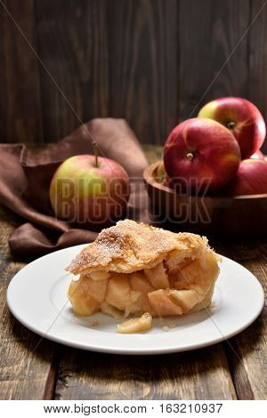 Piece of apple pie ad fresh fruits on wooden table