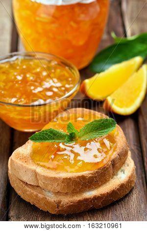 Orange jam on toast bread over wooden table