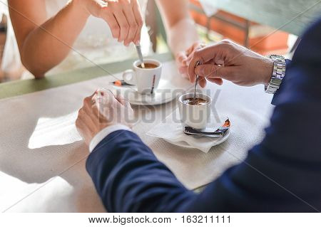 Happy bride and groom sitting in the cafe at the table. Loving bride and groom drinking coffee at the table.