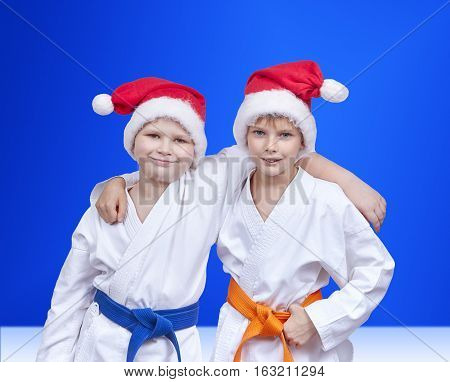 On a blue background boys in caps of Santa Claus