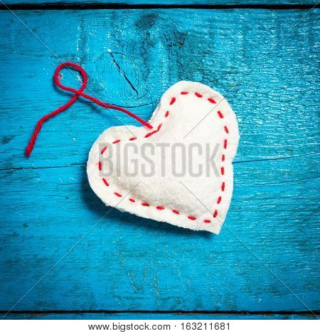 Valentine's Day. Colorful knitted hearts. White heart on the blue boards. Valentines day. Heart pendant. Red heart. Valentine cards. Space for text. Eighth of March. International Women's Day.