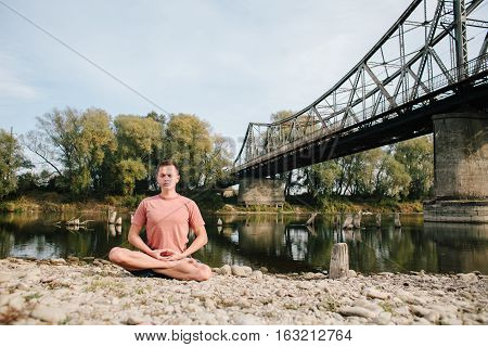 man practices yoga on the river bank near the old bridge. lotos