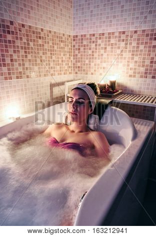 Beautiful woman with closed eyes lying in tub doing hydrotherapy treatment. Health and beauty concept.