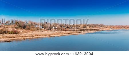 Panoramic View Of Village On The Overgrown Hill Near Yellowed Riverbank In Spring Autumn Sunny Day Under Blue Clear Sky. Copy Space. Panorama