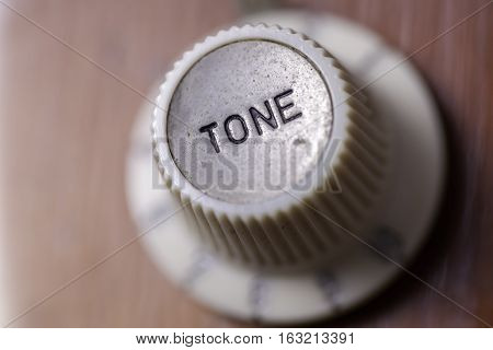 Vintage tone. Focus on a retro tone dial from a vintage guitar.