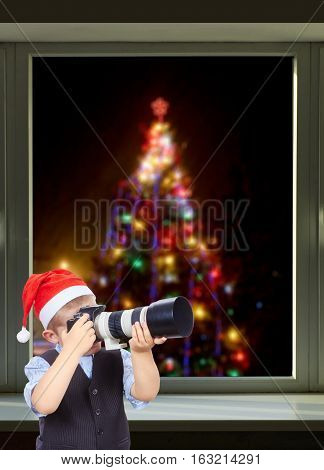 Little photographer on the background of beautiful Christmas tree outside the window
