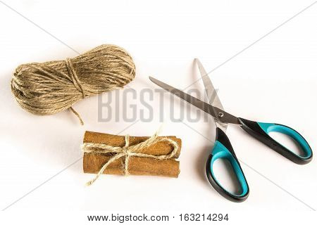 Bundle of cinnamon with scissors and skein of twine