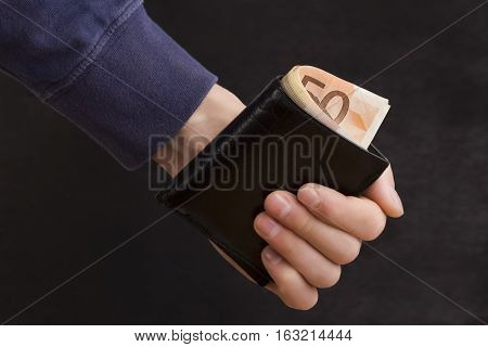 man holding a purse with money in hand