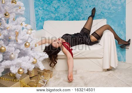 Strangled Beautiful Woman In Black Dress Lies Near The Christmas Tree On The Couch
