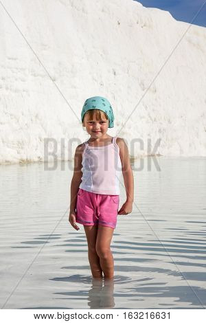 Smiling toddler girl posing like a pro model standing in nature pool against white rock in Pamukkale