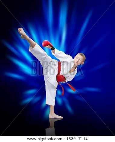 Roundhouse kick an athlete beats on the background of blue rays