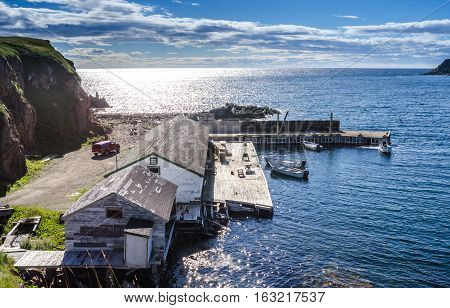 Twillingate, Newfoundland, man works on the engine of one of 4 boats tied up to a wooden, cliff-side dock house for the day, bright sunshine on calm coastal water.