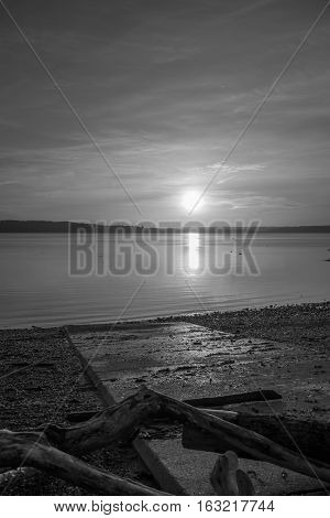 Luminous light envelops everything as the sun sets over the Puget Sound. Black and white image.
