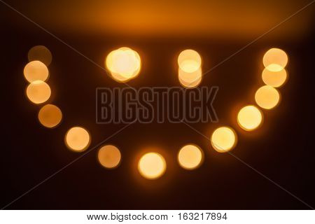 winking smiley of the candles on dark black background
