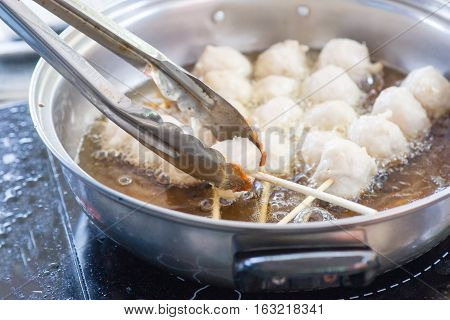 Meatballs Frying in Vegetable Oil in Iron pan on electric stove